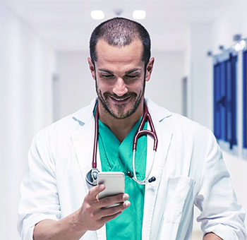 Male doctor checking his schedule on a smartphone.