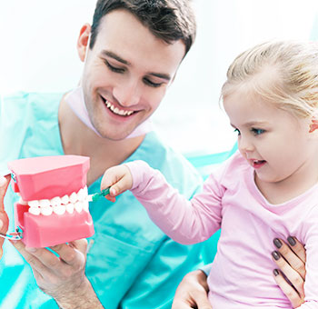 Dentist showing to a patient how to brush teeth correctly.