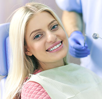 Woman patient smiling in dental chair after a teeth whitening treatment.