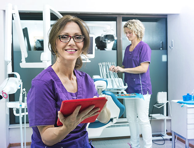 Woman dentist managing appointments on a tablet and preparing for next dental care patient.