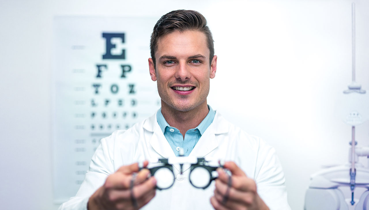 Optician handing messbrille glasses during eye test.