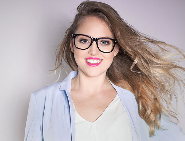 Smiling woman showcasing newly prescribed corrective lenses.